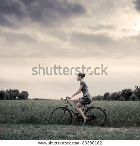 Vintage portrait of a woman riding a bike in a field - stock photo