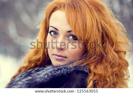 Vintage portrait of a young red-haired girl on the street