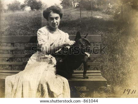 Vintage portrait of a young woman and her black dog sitting on a park bench.  Original Circa 1911 print has scratches, artifacts, fading and solarization qualities. - stock photo