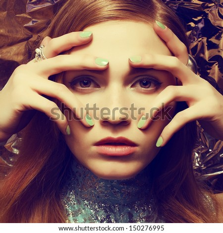 Vintage portrait of beautiful woman with long healthy shiny red (ginger) hair, perfect makeup and stylish silver accessories on her hands. Hands on face. Close up. Retro-futurism style - stock photo