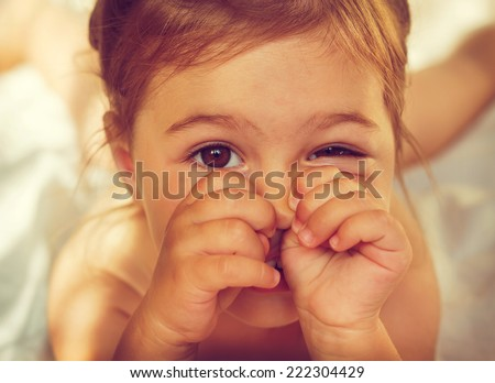 vintage portrait of Cute Little girl making funny face on the carpet in my room  - stock photo