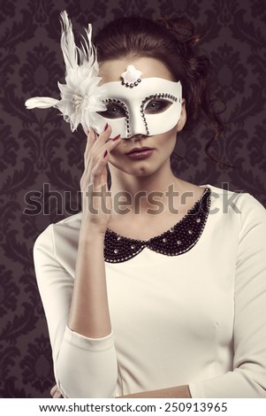 vintage portrait of nice woman , in elegant white dress and mask looking in camera . ready for party - stock photo