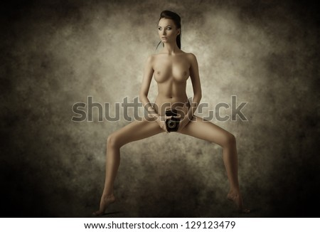 vintage portrait of nude sexy woman brunette with old camera on pubis - stock photo
