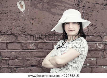 Vintage portrait of pretty young woman against brick wall background. Woman in white hat. Toned photo with copy space. Vintage style photo. - stock photo