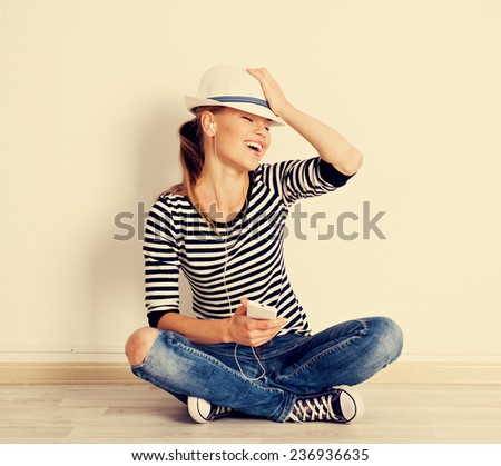 Vintage portrait of singing girl sitting at empty wall at home. Young attractive female enjoying music in headset. Lifestyle and leisure concept. - stock photo