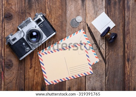 Vintage post card and envelope with retro camera on old wooden table - stock photo