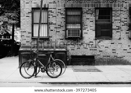 Vintage postcard of beautiful building, entrance door and bicycle, Manhattan New York, USA. Classic apartment in New York City. Black and white photo. Retro travel picture. - stock photo