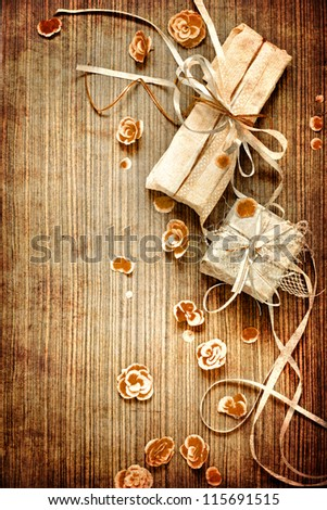 Vintage Present,gift bow with petal from flowers on wooden table/valentin day background - stock photo