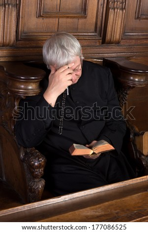Vintage priest dressed in black cassock reading and holding a rosary - stock photo