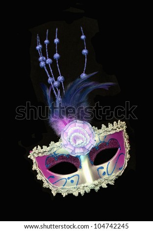 Vintage purple / pink and silver dress mask with feathers and flower isolated on a black background - stock photo
