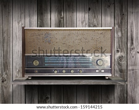 Vintage radio receiver device on old wooden shelf
