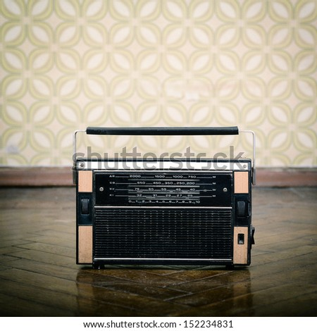 vintage radio receiver device on the weathered wooden parquet floor in vintage room with old fashioned wallpaper, toned and noise added - stock photo