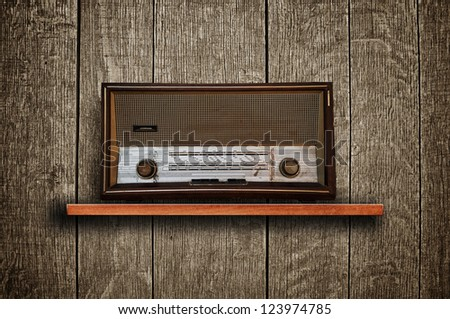 Vintage radio receiver device on wooden shelf