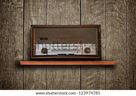 Vintage radio receiver device on wooden shelf - stock photo