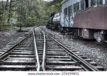 Vintage railroad tracks with abandoned train