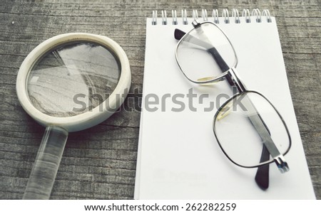 vintage reading glasses, magnifying loupe, note pad, diary, diary on wooden background - stock photo
