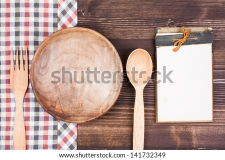 Vintage recipe cookbook, tablecloth, spoon, fork on wood background - stock photo