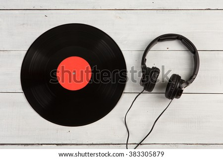 Vintage record LP and headphones on the wooden background - stock photo
