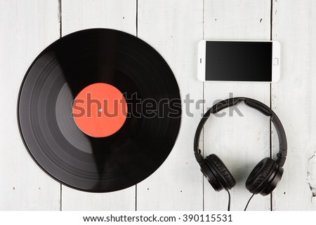Vintage record LP, smartphone and headphones on the wooden background - stock photo