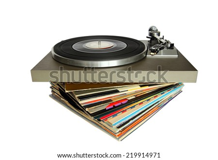Vintage record player on a stack of old vinyls isolated - stock photo