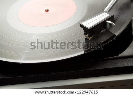 Vintage record player with spinning vinyl. - stock photo