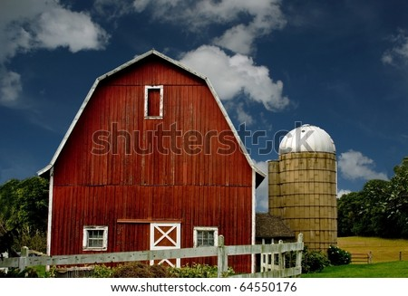 vintage red barn and silo with a white fence against a blue sky - stock photo