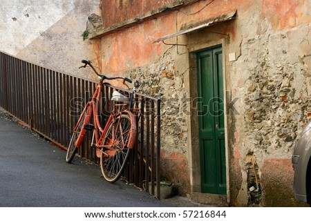 Vintage red bicycle in European village - stock photo