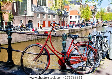 Vintage red bicycle tied up near an canal in Amsterdam, Netherlands