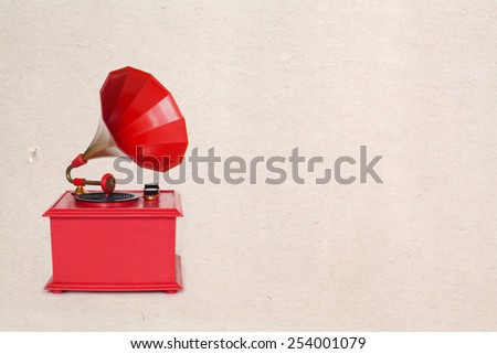 Vintage red color gramophone. Retro plastic toy. Old paper background and texture - stock photo