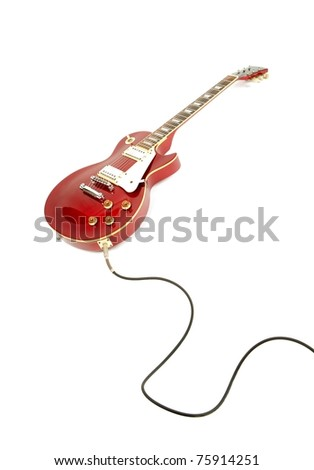 Vintage red electric solid body guitar plugged in with instrument cable in its sides jack. Isolated on white. - stock photo