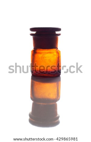 Vintage red glass bottle isolated on white background with reflection - stock photo