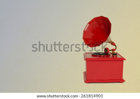 Vintage red gramophone. Retro plastic toy. Old paper background and texture - stock photo