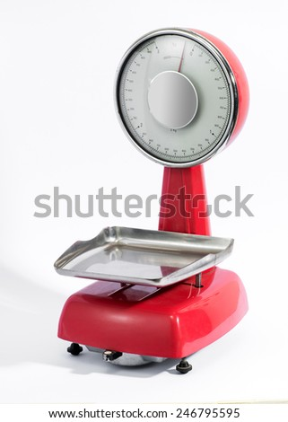 Vintage red scale with silver metal pan and circular dial for measuring merchandise in a store, over white - stock photo