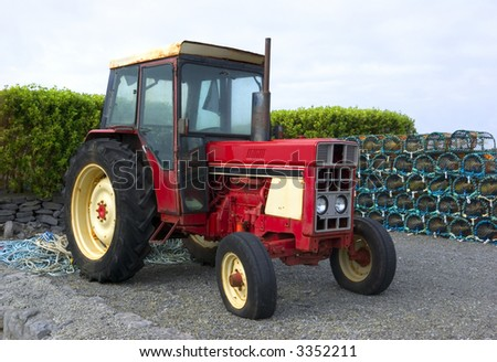 Vintage red tractor in front of a pile of lobster pots, photographed in Connemara, County Galway, Ireland - stock photo
