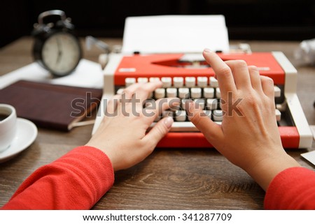 Vintage red typewriter with blank paper on wooden desk - stock photo