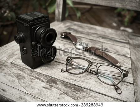 Vintage retro accessory. camera, eyeglasses and watch on wooden background ( Vintage tone color ) - stock photo