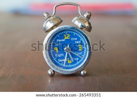 Vintage retro alarm clock on table - stock photo