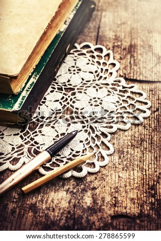 Vintage retro background,  old retro book and hand made white doily on old wooden table - stock photo