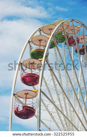 Vintage retro carousel in focus. Vivid colors on bright blue sky. - stock photo