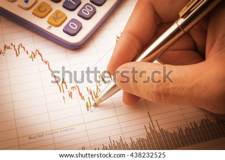 Vintage / retro color : Chart / graph of financial instruments for technical trend analysis has been analysed by businessman / equity analyst with a pen pointing on red / green candle stick signal. - stock photo