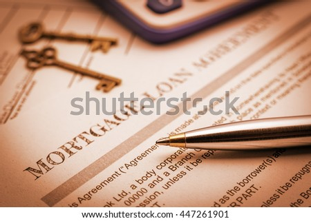 Vintage / retro color style : Closeup view of a blue ballpoint pen, vintage brass keys and a mortgage loan agreement. A form is waiting to be checked and reviewed by a homeowner or a borrower. - stock photo