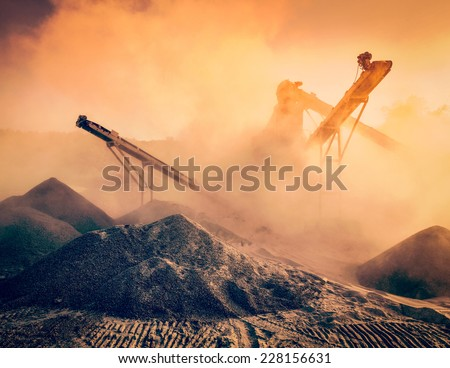 Vintage retro effect filtered hipster image of Industrial hell pollution background concept - crusher (stone crushing machine) at open pit mining processing plant for crushed stone sand and gravel  - stock photo