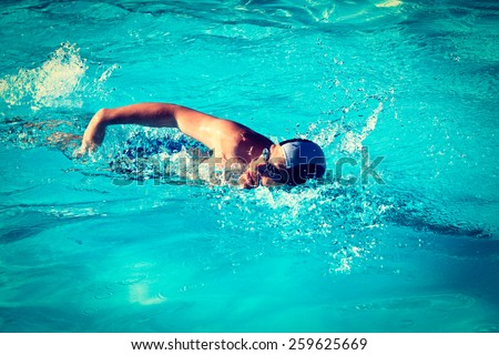 Vintage retro effect filtered hipster style image of athletic Man swimming in the pool - stock photo