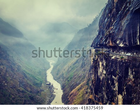 Vintage retro effect filtered hipster style image of car on dangerous road in Himalayas mountains in gorge above precipice