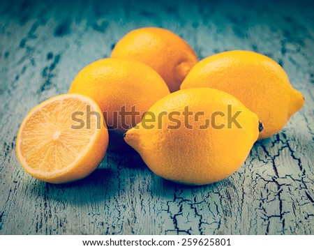 Vintage retro effect filtered hipster style image of five fresh ripe yellow lemons on blue wooden background - stock photo