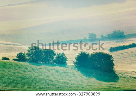 Vintage retro effect filtered hipster style image of Moravian rolling fields landscape in morning mist. Moravia, Czech Republic - stock photo