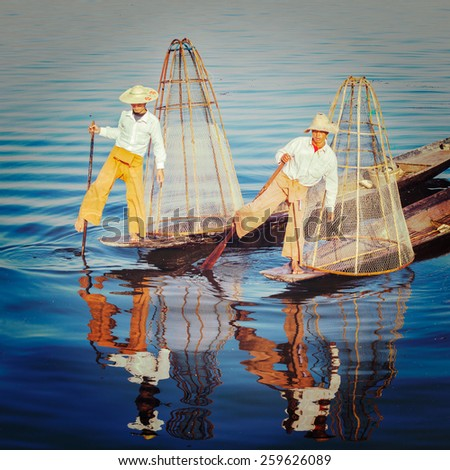 Vintage retro effect filtered hipster style image of Myanmar traditional Burmese fishermen with fishing net at Inle lake in Myanmar famous for their distinctive one legged rowing style - stock photo