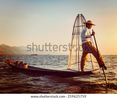 Vintage retro effect filtered hipster style image of Myanmar travel attraction landmark - Traditional Burmese fisherman at Inle lake, Myanmar famous for their distinctive one legged rowing style - stock photo