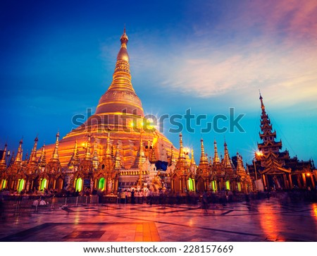 Vintage retro effect filtered hipster style image of Myanmer famous sacred place and tourist attraction landmark - Shwedagon Paya pagoda illuminated in the evening. Yangon, Myanmar (Burma) - stock photo