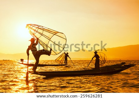 Vintage retro effect filtered hipster style image of three Myanmar traditional Burmese fishermen at Inle lake, Myanmar famous for their distinctive one legged rowing style - stock photo